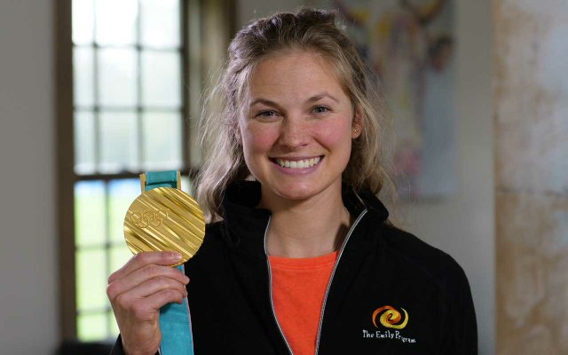 Jessie Diggins holding up her Olympic gold medal