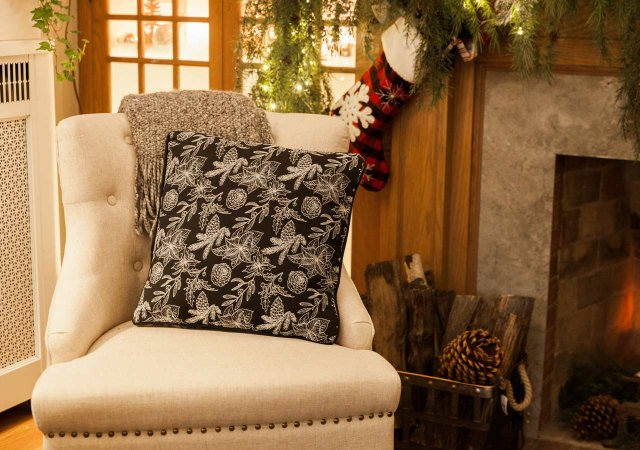 Patterned pillow on a chair near the fireplace