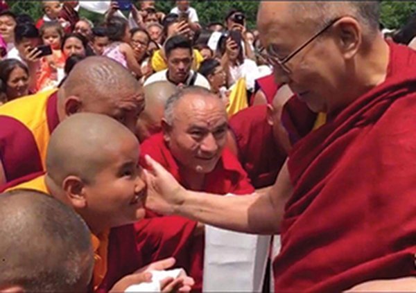 Jalue Dorje getting blessed by the Dalai Lama