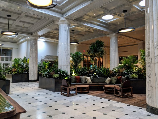 Lots of plants and lounge seating in the lobby.