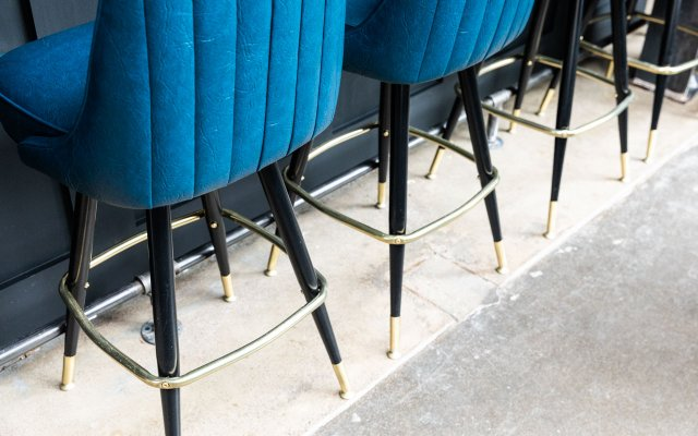 Barstools with blue upholstery and black legs at Cobble Social House