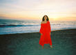 Woman on a beach in a red dress from MILLE Collection