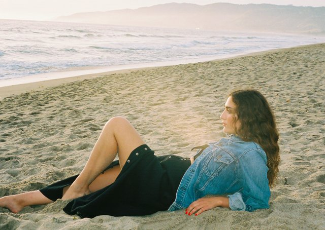 woman on a beach in a black dress and denim jacket from MILLE Collection