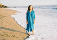 Woman on a beach wearing a blue dress from MILLE Collection