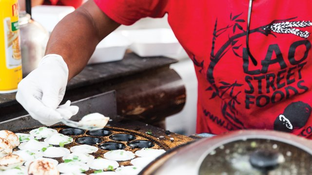 Lao Street Foods whips up orders of khao nom kok (coconut rice pancakes)