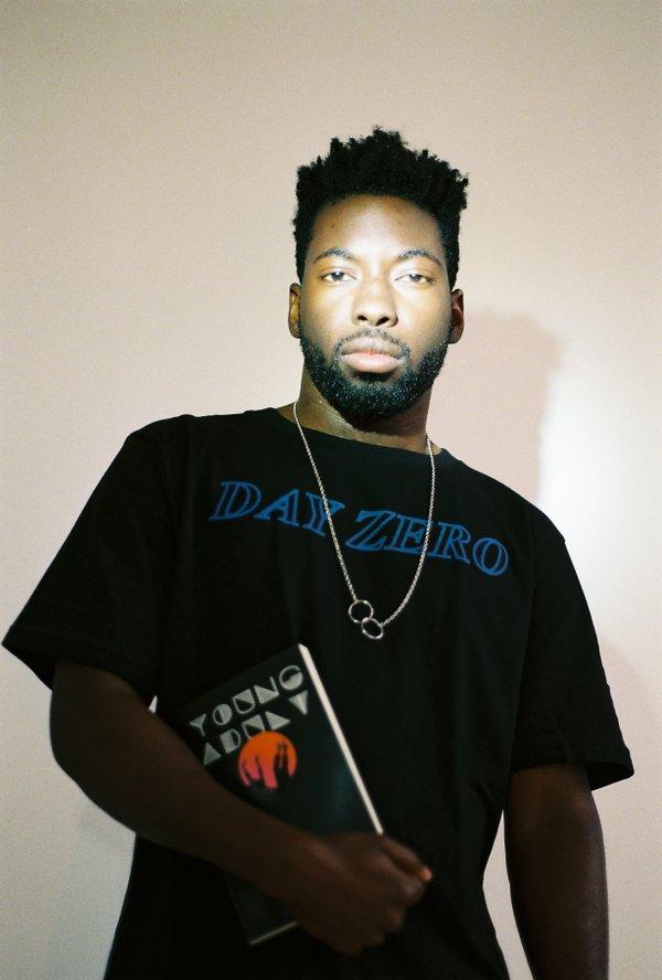 Man wearing a black t shirt holding a book