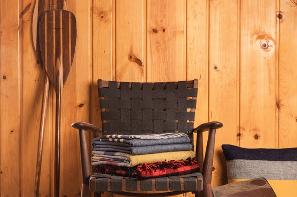 Oars, chair, woolen blankets, leather satchel, coffee cup, and rug