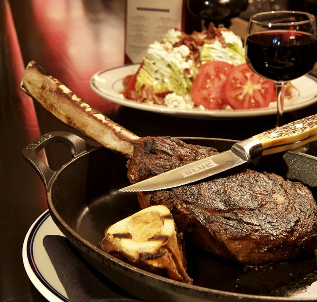a ribeye steak, salad, and glass of red wine