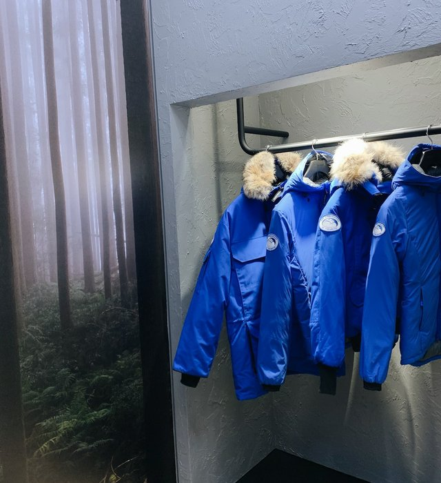 four blue jackets hanging on a rack