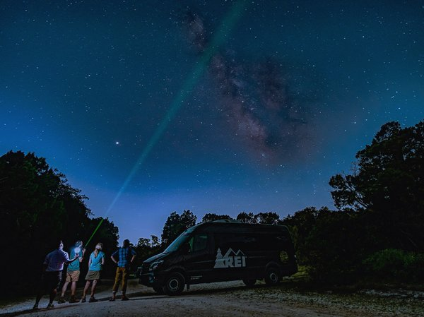 four people gazing up at the night sky with a chunk of the milky way visible
