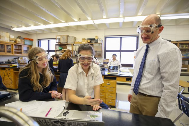 students and teacher in a science class wearing safety goggles