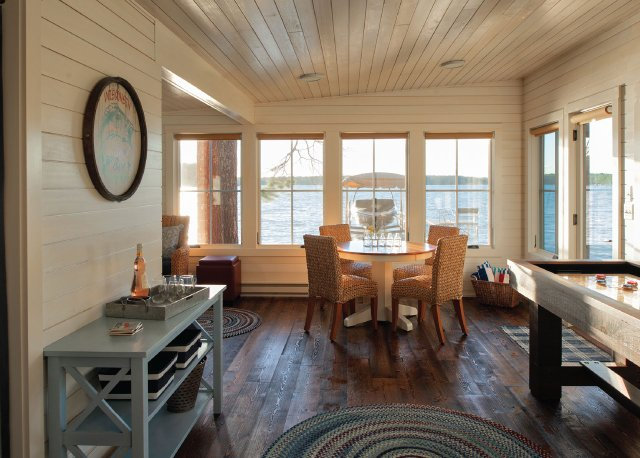 Cabin interior with white shiplap walls looking over a lake