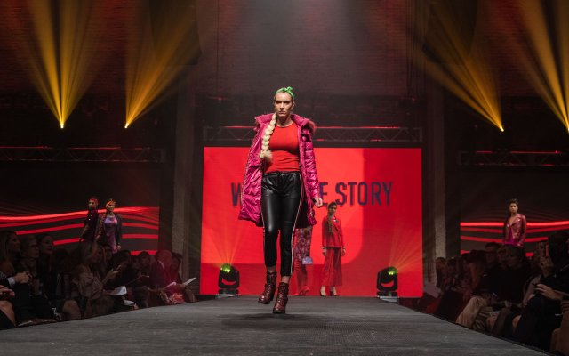 Fashionopolis 2019: woman on runway wearing black leather pants, red top and pink puffy coat