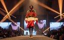 Fashionopolis 2019: woman on runway wearing red dress and brown fur coat