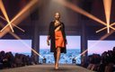 Fashionopolis 2019: woman on runway wearing orange skirt, striped top, and long black coat