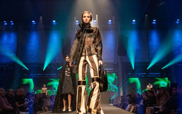 Fashionopolis 2019: woman on runway wearing brown and white pants, sheer blouse and brown jacket
