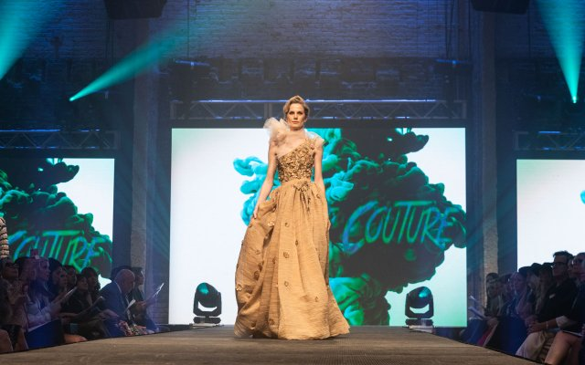 Fashionopolis 2019: woman on runway wearing long off-the-shoulder gown with wrap scarf