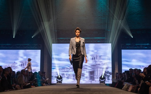 Fashionopolis 2019: woman on runway wearing black dress, blazer and brown suede boots