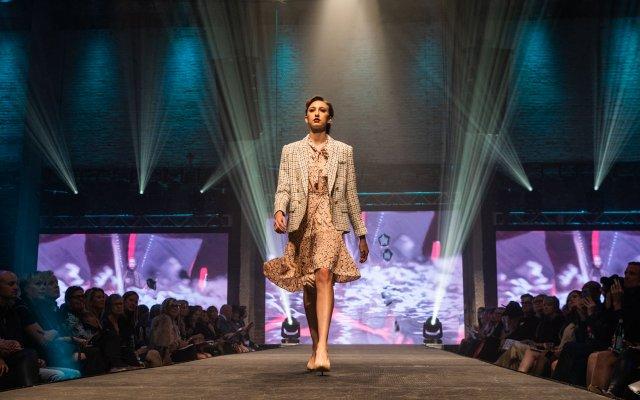 Fashionopolis 2019: woman on runway wearing patterned dress and plaid blazer