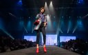 Fashionopolis 2019: woman on runway wearing denim jeans, blue top, plaid jacket and red shoes