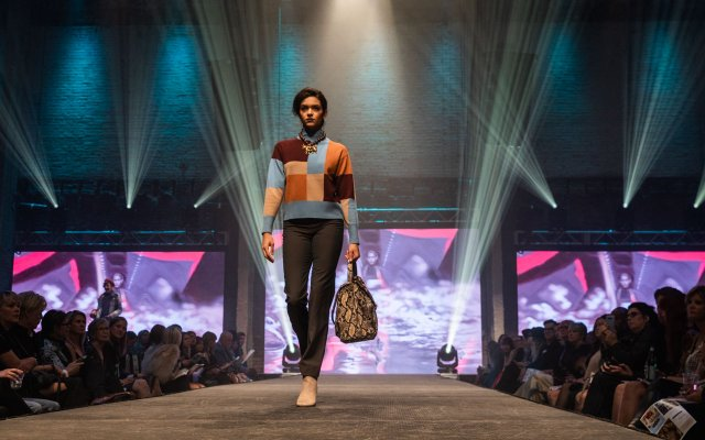 Fashionopolis 2019: woman on runway wearing black pants and color block sweater