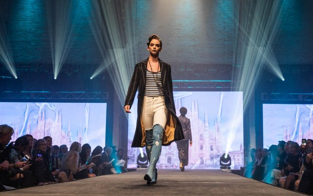 Fashionopolis 2019: woman on runway wearing white pants, striped tank, long black coat and tall blue boots