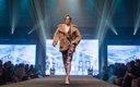 Fashionopolis 2019: woman on runway wearing patterned dress and brown fur coat