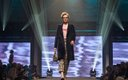 Fashionopolis 2019: woman on runway wearing plaid pants, graphic t-shirt, and long double-breasted coat