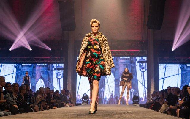 Fashionopolis 2019: woman on runway wearing butterfly print dress and animal print coat