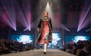 Fashionopolis 2019: woman on runway wearing red patterned pleated dress and fur coat