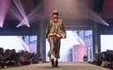 woman on runway at Fashionopolis 2019: woman on runway wearing striped pants, leopard print top and blazer, with red necklace