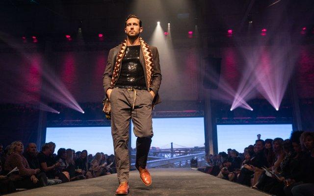 Fashionopolis 2019: man on runway wearing brown pants, sequin top, coat and scarf