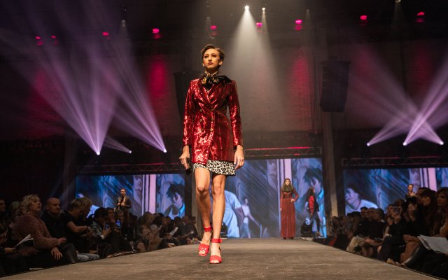 Fashionopolis 2019: woman on runway wearing short leopard print dress, shiny red trench coat and brown scarf