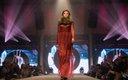 Fashionopolis 2019: woman on runway wearing long red print dress with fur collar
