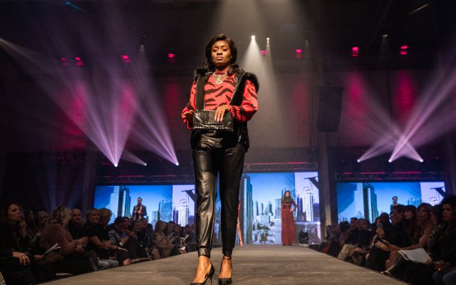 Fashionopolis 2019: woman on runway wearing black leather pants, red animal striped sweater, and fur vest