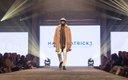 Fashionopolis 2019: man on runway wearing white pants, brown shirt, brown coat and plaid scarf