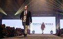 Fashionopolis 2019: man on runway wearing plaid suit, brown tie and brown coat