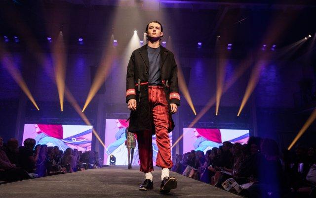 Fashionopolis 2019: man on runway wearing red pant, gray sweatshirt and black coat