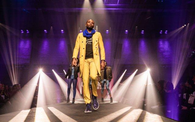 Fashionopolis 2019: man on runway wearing yellow pant, black graphic t-shirt, yellow coat and blue scarf
