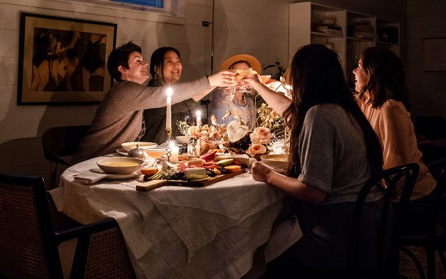 group of people cheersing at the dinner table