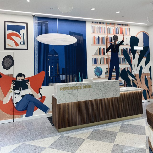 front desk with colorful mural behind it