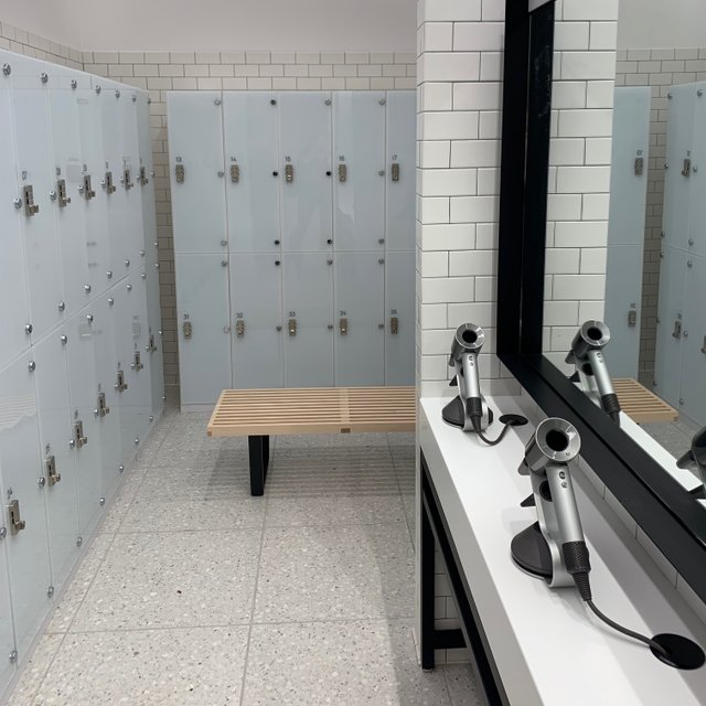 women's locker room counter and mirror with hair dryers and lockers in the background