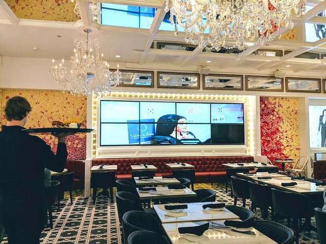 dining room with large video screen on the back wall