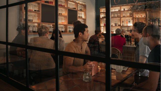 Window peek into bar scene.