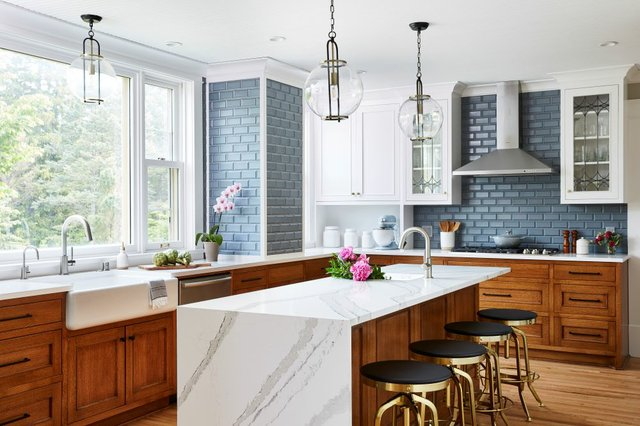 Natural light is utilized to brighten the space. There is a balance with light wooden cabinetry on the bottom and white built-in upper cabinetry. The marble counter on the island extends to the floor.
