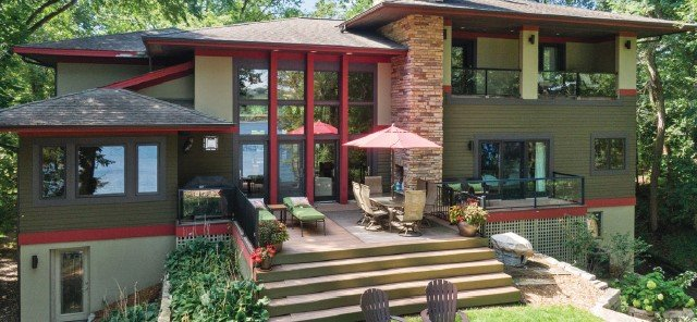 Home with red trim surrounded by forest