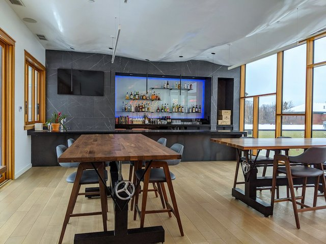 open space with a bar and high top tables with chairs