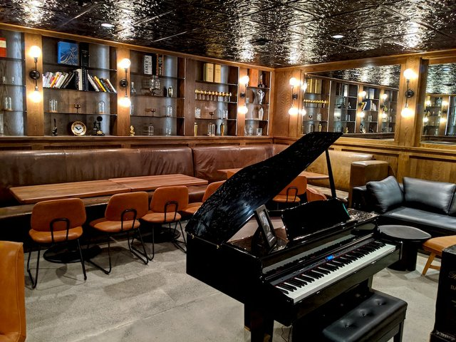 a lounge with a piano in the middle of the room