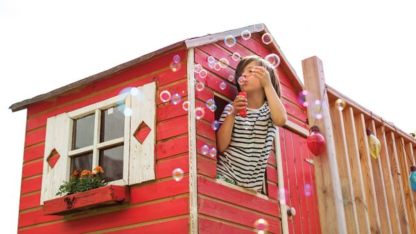 Kid blowing bubbles out the window of a playhouse