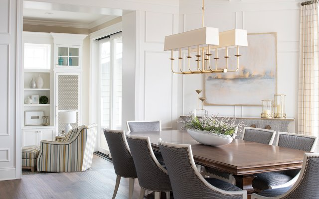 Brown dining table with chairs upholstered in blue-gray fabric with gold detailing